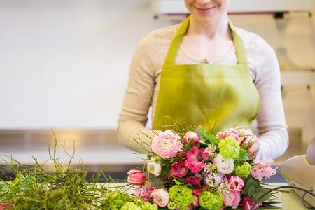 mensen, het bedrijfsleven, de verkoop en bloemisterij concept - close-up van de bloemist vrouw die bos in bloemenwinkel