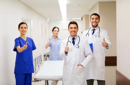 gurney: clinic, profession, people, health care and medicine concept - group of happy medics or doctors with gurney showing thumbs up at hospital corridor Stock Photo