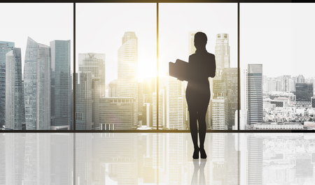 business and people concept - silhouette of woman with folders over office window and singapore city skyscrapers background and sun light photo