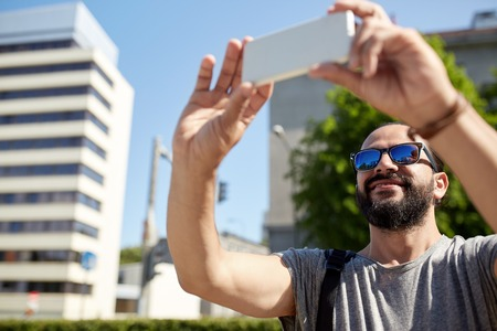 taking video: travel, tourism, communication, technology and people concept - smiling man with backpack taking video or selfie by smartphone on summer city street