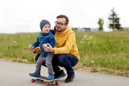 father and son: family, childhood, fatherhood, leisure and people concept - happy father teaching little son to ride on skateboard