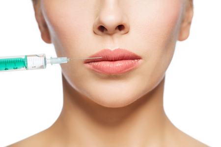 augmentation: people, cosmetology, plastic surgery and beauty concept - beautiful young woman face and syringe making injection for lips augmentation over white background
