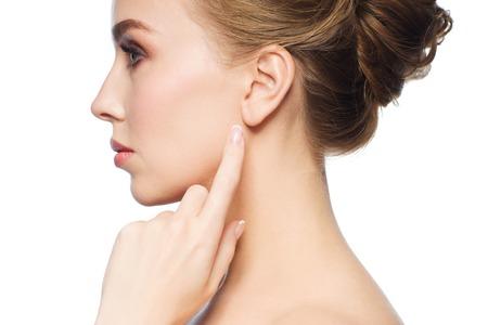Gesundheit, Menschen und Beauty-Konzept - schöne junge Frau zeigt mit dem Finger an ihr Ohr auf weißem Hintergrund