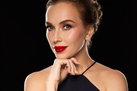 femme fatale: people, luxury and fashion concept - beautiful woman in black with red lips over dark background Stock Photo