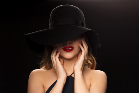 black hat: people, luxury and fashion concept - beautiful woman in black hat over dark background Stock Photo
