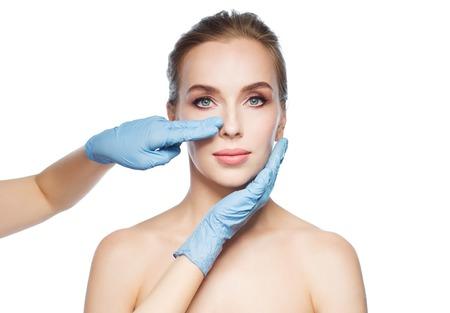 pessoas, cosmetologia, a cirurgia plástica e beleza conceito - face da mulher tocando cirurgião ou mãos esteticista sobre o fundo branco