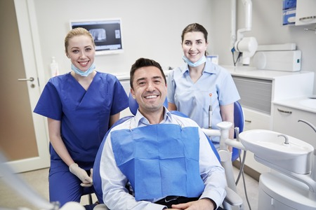 people, medicine, stomatology and health care concept - happy female dentists with man patient at dental clinic office Stock Photo