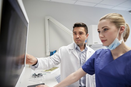roentgen: people, medicine, stomatology, technology and health care concept - dentists looking to x-ray scan on monitor at dental clinic