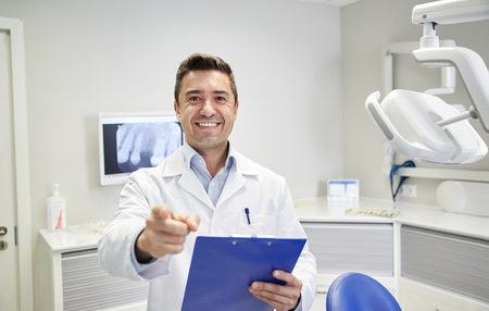 stomatological: people, medicine, stomatology and healthcare concept - happy middle aged male dentist in white coat at with clipboard pointing finger to you at dental clinic office Stock Photo