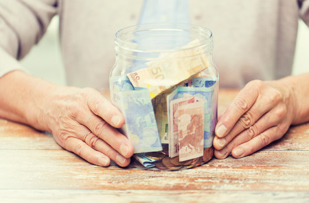 retirement money: savings, money, annuity insurance, retirement and people concept - close up of senior woman hands with money in glass jar