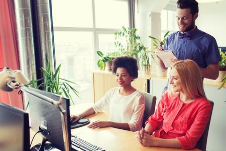 negocios internacionales: negocio, puesta en marcha y la gente concepto - equipo creativo feliz con el ordenador portátil y en la oficina Foto de archivo