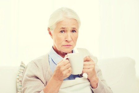 home health care: health care, flu, cold, age and people concept - sick senior woman with paper napkin drinking hot tea at home Stock Photo