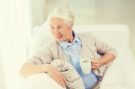 woman drinking tea: age, drink and people concept - happy smiling senior woman with cup of tea at home