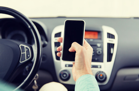 transport, business trip, technology and people concept - close up of young man hand with smartphone driving car Stock Photo