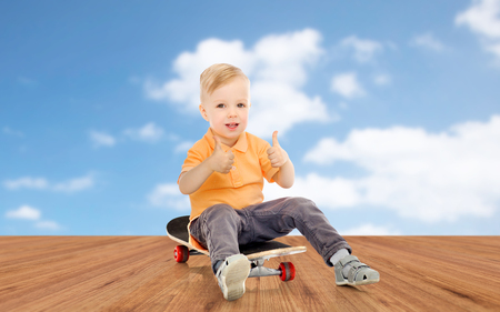 kiddy: childhood, sport, leisure, gesture and people concept - happy little boy sitting on skateboard and showing thumbs up over blue sky and wooden floor background Stock Photo