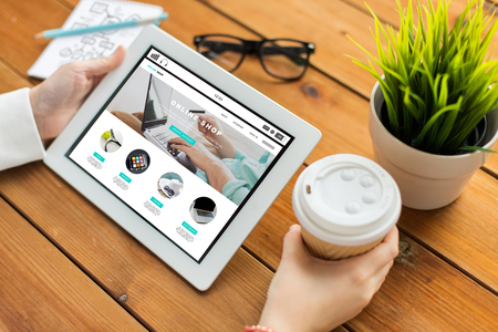 business, internet shopping, technology and people concept - close up of woman with online shop web page on tablet pc computer screen, notebook and coffee on wooden table 写真素材