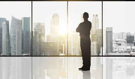 Concept d'entreprise et de personne - silhouette d'homme d'affaires sur la fenêtre du bureau et la ville de Singapour gratte-ciel fond et lumière du soleil