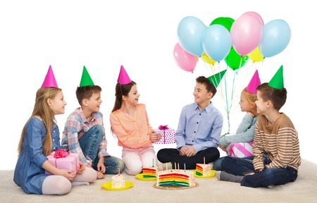 childhood, holidays, celebration, friendship and people concept - happy smiling children in party hats with cake giving presents at birthday party