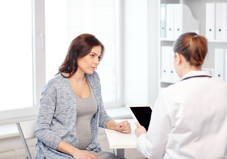 pregnancy, gynecology, medicine, health care and people concept - gynecologist doctor with tablet pc computer and pregnant woman meeting at hospital