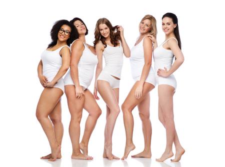 skinny: amistad, belleza, cuerpo positivo y concepto de la gente - grupo de mujeres felices diferentes en ropa interior blanca Foto de archivo