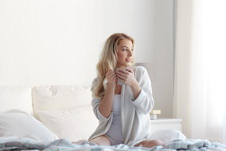 아침, 레저 및 사람들이 개념 - 집에서 침실에 커피 또는 홍차 한잔 하 고 행복 한 젊은 여자 침실