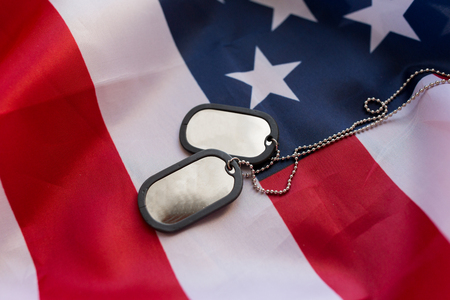 nationalism: military forces, military service, patriotism and nationalism concept - close up of american flag and soldiers badges