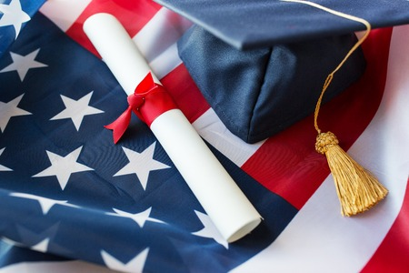 nationalism: education, graduation, patriotism and nationalism concept - close up of bachelor hat and diploma on american flag Stock Photo