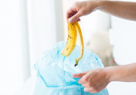 food waste: recycling, food waste, garbage, environment and ecology concept - close up of hand putting banana peel into rubbish bag at home