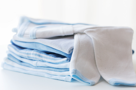 folded clothes: clothing, babyhood, motherhood and object concept - close up of white baby cardigan with pile of folded clothes for newborn boy Stock Photo