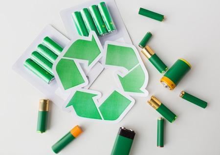 alkaline: waste recycling, garbage disposal, environment and ecology concept - close up of used alkaline batteries and green recycling symbol