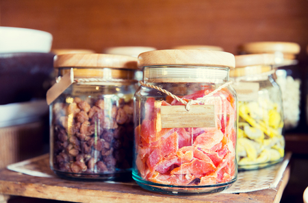 glass jars: food, storage and eating concept - close up of jars with dried fruits at grocery Stock Photo