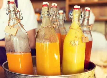 음료, 갈증, 다과 및 판매 개념 - 시장에서 얼음 양동이에 과일이나 야채 주스 병