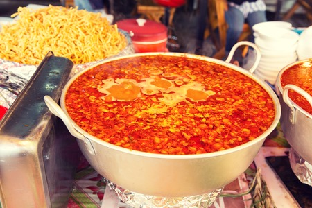 spicy cooking: cooking, asian kitchen, sale and food concept - pot of spicy soup at street market Stock Photo