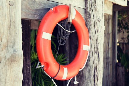life saving: summer, beach, swimming and life saving concept - lifebuoy or life preserver hanging on rescue booth