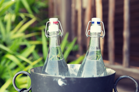 water bottles: drinks, thirst, refreshment and summer resort concept - couple of water bottles in ice bucket at hotel