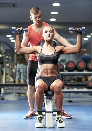 man gym: sport, fitness, bodybuilding, lifestyle and people concept - man and woman with dumbbells flexing muscles in gym