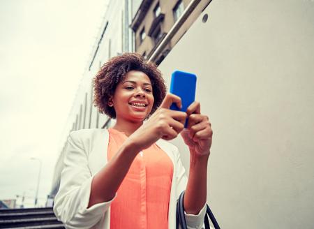 down the stairs: negocios, la tecnología, la comunicación y el concepto de la gente - joven sonriente africano americano de negocios con el teléfono inteligente al bajar escaleras en paso subterráneo de la ciudad Foto de archivo