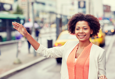 catching taxi: business trip, transportation and people concept - young smiling african american woman catching taxi at city street