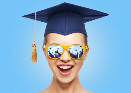 graduation, education, school and people concept - happy screaming teenage girl in shades and mortarboard or bachelor hat over blue background Stock Photo