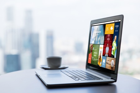 working desk: technology, internet, media, business and modern life concept- close up of open laptop computer with news web page on screen and coffee cup on table at office or hotel room Stock Photo