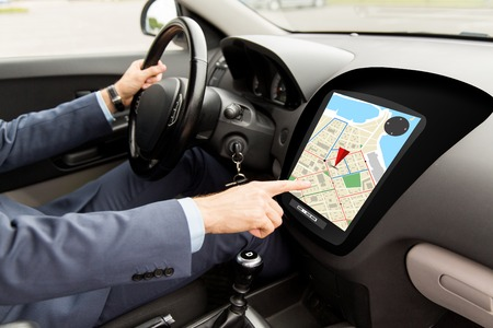onboard: transport, destination, navigation, modern technology and people concept - close up of man driving car with gps navigator map on board computer screen
