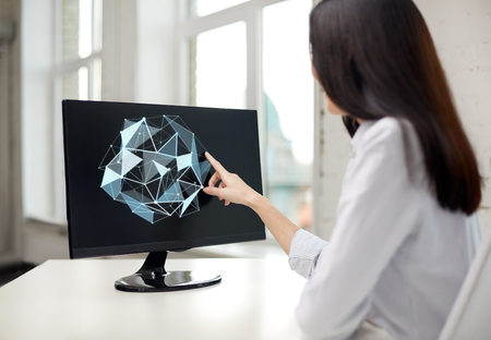 virtual technology: people, business, virtual reality and technology concept - businesswoman touching monitor with virtual low poly shape projection on screen in office