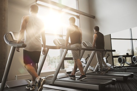 hombres haciendo ejercicio: sport, fitness, lifestyle, technology and people concept - men exercising on treadmill in gym Foto de archivo
