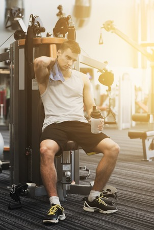 young male: sport, fitness, equipment, lifestyle and people concept - man exercising on gym machine