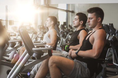 sportsmen: sport, fitness, lifestyle, technology and people concept - men working out on exercise bike in gym