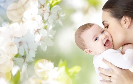 家族、母性、子育て、人と保育コンセプト - 幸せな母上の緑の自然背景かわいい赤ちゃんのキス