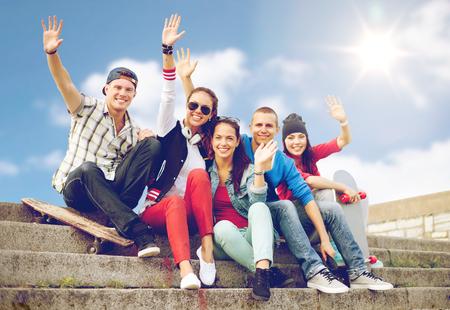 vacaciones de verano y el concepto de adolescentes - grupo de adolescentes sonrientes colgando fuera y agitando las manos