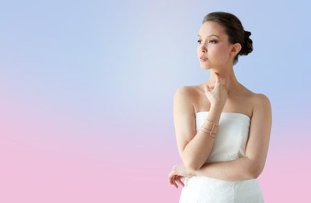 bride bangle: beauty, jewelry, wedding accessories, people and luxury concept - beautiful asian woman in white dress or bride with golden bracelet over rose quartz and serenity gradient background
