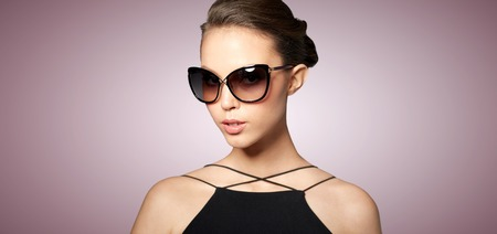 eyewear fashion: accessories, eyewear, fashion, people and luxury concept - beautiful young woman in elegant black sunglasses over violet background
