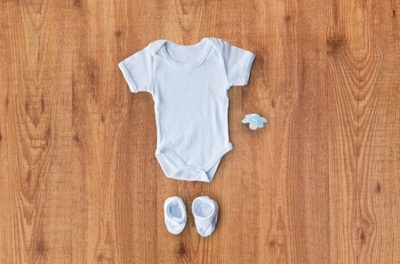 bootees: baby clothes, babyhood, motherhood and object concept - close up of white bodysuit, bootees and soother for newborn boy on wooden table